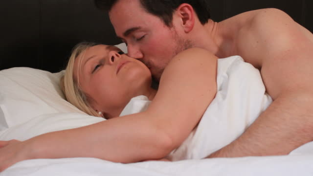 couple kissing and spooning in bedroom - arm around stock videos and b-roll footage
