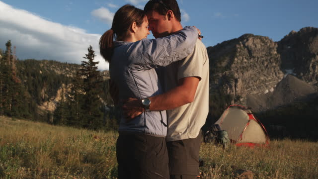couple kissing at their campsite