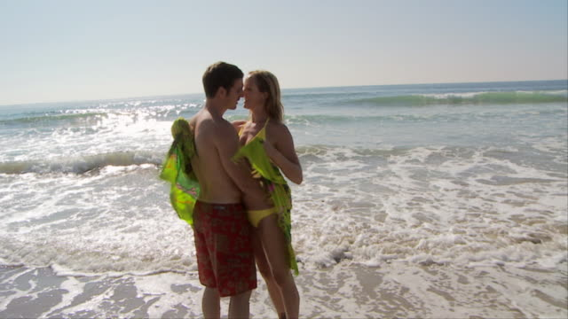 slo mo of couple kissing at waters edge at the beach - badeshorts stock-videos und b-roll-filmmaterial
