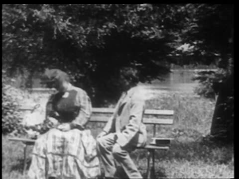B/W 1902 couple kissing + flirting on park bench / man kneels to propose