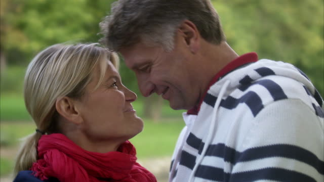 a couple kissing in a park, sweden. - sideways glance stock videos & royalty-free footage