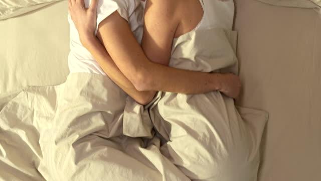 stockvideo's en b-roll-footage met couple kissing in bed - kussen beddengoed