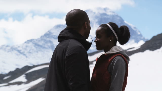 couple kissing in front of snowcapped mountains