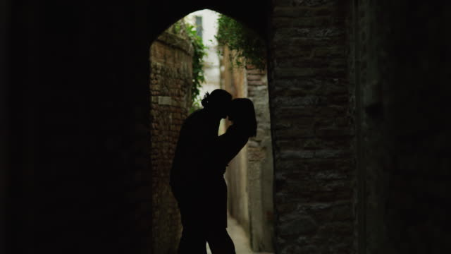 vídeos de stock e filmes b-roll de ws couple kissing in narrow old town alley / venice,veneto - retroiluminado
