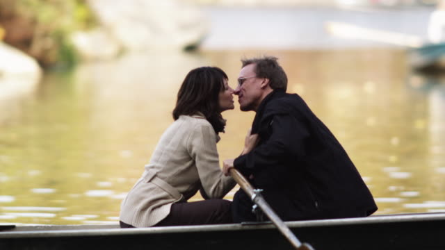ms pan couple kissing in row boat at central park lake / new york city, new york state, usa - wasserfahrzeug stock-videos und b-roll-filmmaterial