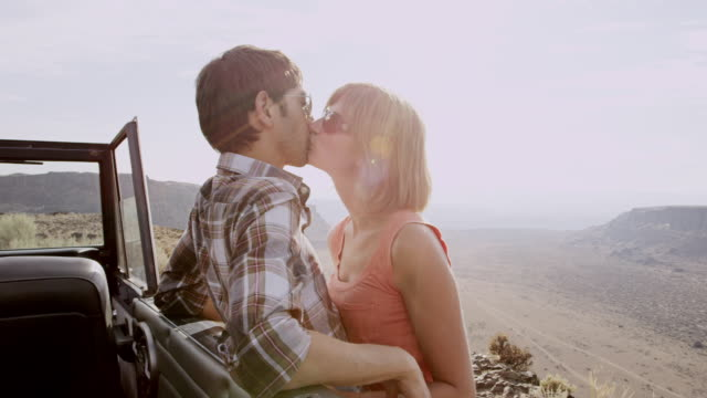 ms tu couple kissing leaning against convertible off road vehicle on side of rural desert road overlooking valley - verlieben stock-videos und b-roll-filmmaterial