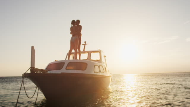 slo mo couple kissing on a boat at sunset - motorboat stock videos & royalty-free footage