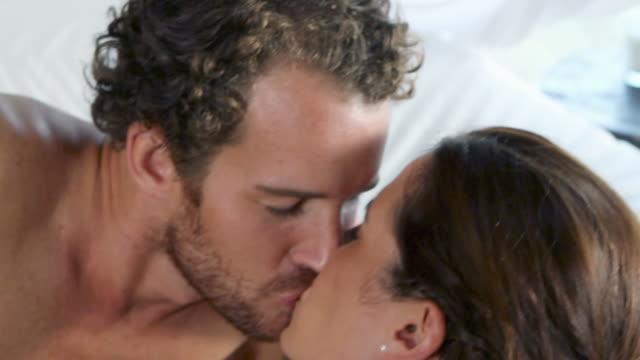 stockvideo's en b-roll-footage met couple kissing on bed, close up - kussen beddengoed