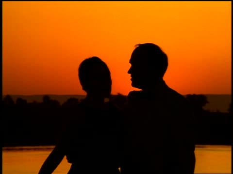 vídeos y material grabado en eventos de stock de orange silhouette couple kissing on deck of cruise ship at sunset / nile river, egypt - crucero vacaciones