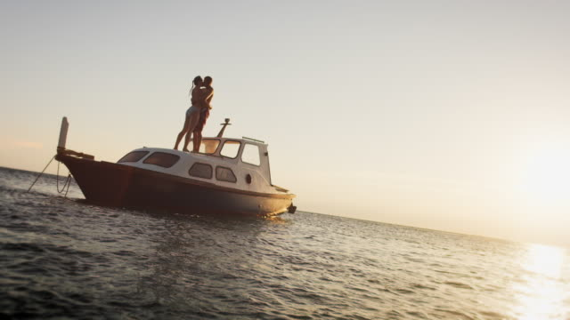 slo mo couple kissing on the boat at sunset - swimming shorts stock videos & royalty-free footage