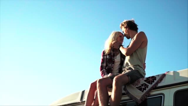couple kissing on van roof during vacation - van vehicle stock videos & royalty-free footage