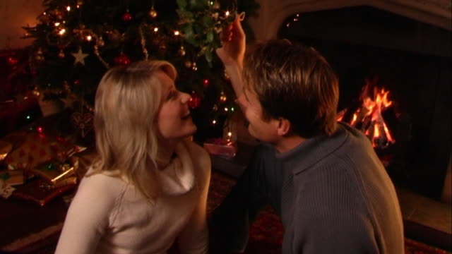 Couple kissing under mistletoe at Christmas.