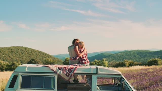 vídeos de stock e filmes b-roll de couple kissing while sitting on van roof - amor