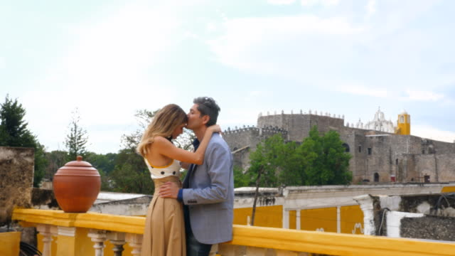 ms couple kissing while standing on hotel rooftop deck over looking city of izamal - anticipation stock videos & royalty-free footage