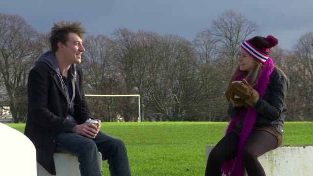 a couple laugh together in the park in winter wide shot - neckwear stock videos and b-roll footage