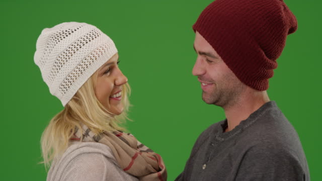 vídeos de stock, filmes e b-roll de couple laughing and talking together in winter clothes at night on green screen - neckwear