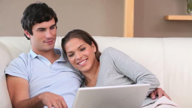 vídeos de stock e filmes b-roll de couple laughing in front of a laptop - em frente de