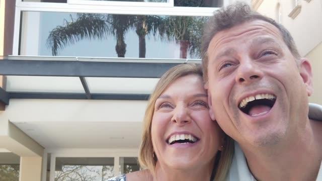家の前で笑うカップル - 見上げる点の映像素材/bロール