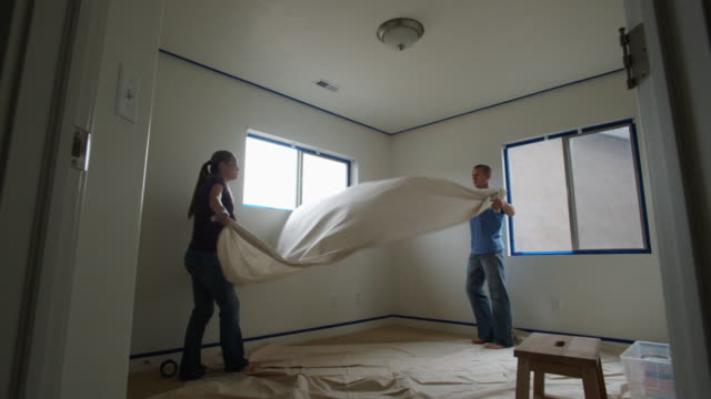 couple laying down drop cloth to paint a room - see other clips from this shoot 1418 個影片檔及 b 捲影像