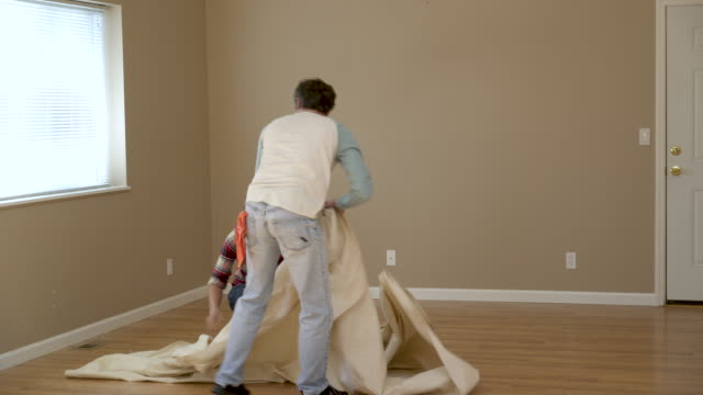 vídeos de stock e filmes b-roll de couple laying dust sheet in room of house. - pano de protecção