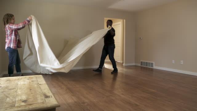 vídeos de stock e filmes b-roll de couple laying dust sheet on floor of new home. - pano de protecção