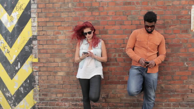 Couple leaning on brick wall outside, looking at cell phones, texting