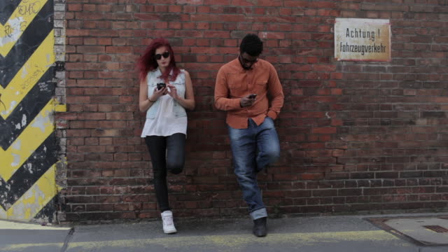 Couple leaning on brick wall outside, looking at cell phones, texting, looking at each other