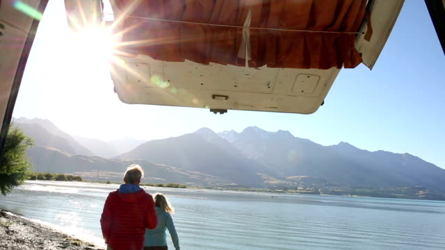 Couple leave camper-van to admire a mountain lake sunrise