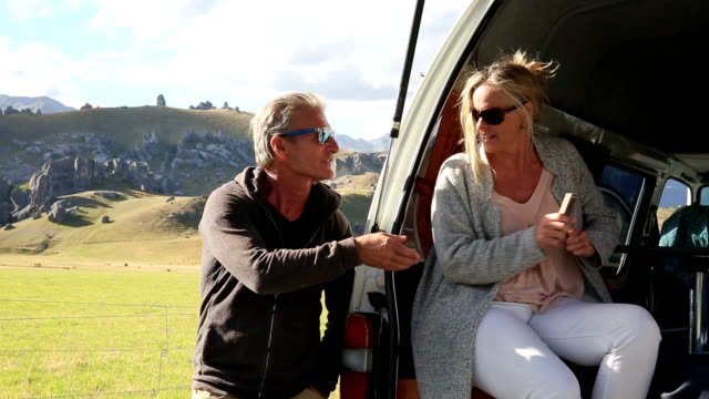 Couple leave campervan to enjoy rural view
