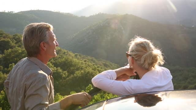 vídeos y material grabado en eventos de stock de couple leave car door, watch sunrise over hills - mano en la barbilla