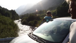 Couple leave car, enjoy view up mountain creek