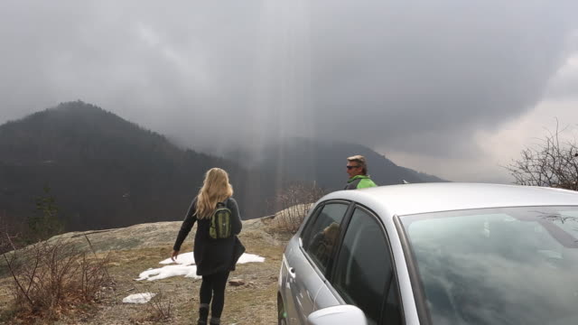 couple leave car to walk to rock overview, shaft of sunlight - gemeinsam gehen stock-videos und b-roll-filmmaterial