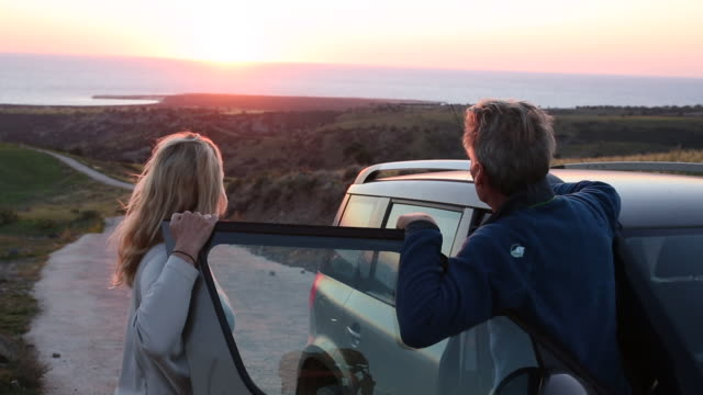 Couple leave vehicle, look out over distant view