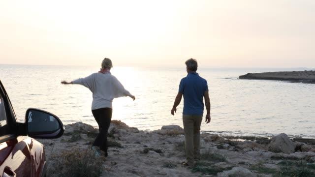 Couple leave vehicle, walk along tidal flat