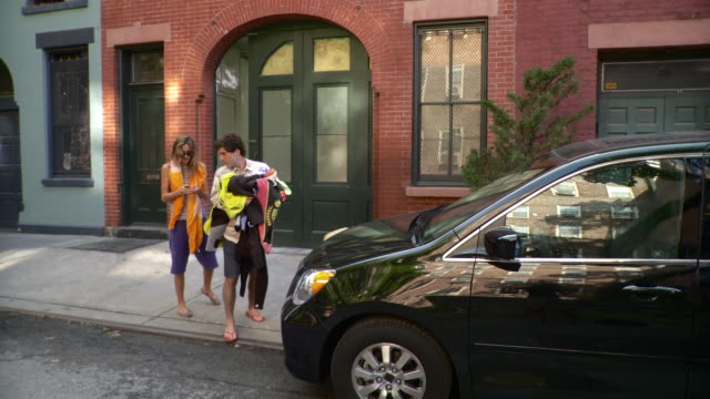 MS PAN Couple leaving building, carrying beach clothes into mini van parked on street / Brooklyn, New York City, New York State, USA