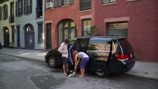 ws couple leaving building, carrying beach clothes into mini van parked on street / brooklyn, new york city, new york state, usa - people carrier stock videos & royalty-free footage