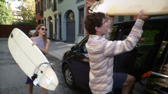 vídeos y material grabado en eventos de stock de ms couple leaving building carrying surfboards, loading them onto mini van parked on street / brooklyn, new york city, new york state, usa - tabla de surf
