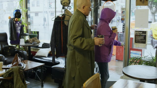 couple leaving coffee shop on rainy day - reusable stock videos & royalty-free footage