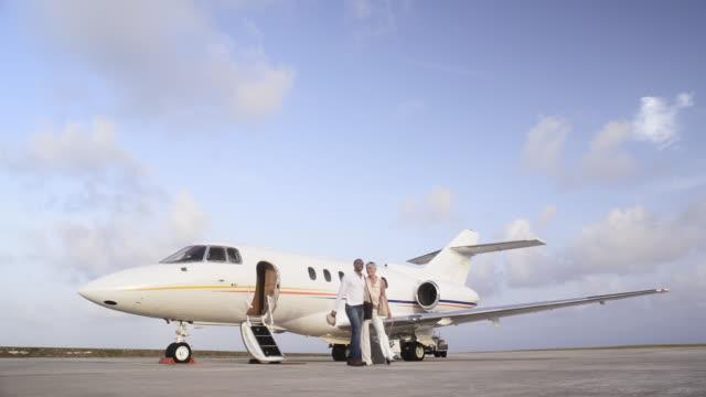 couple leaving private jet - coppia di giovani video stock e b–roll