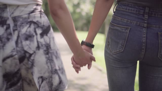 couple lesbian  hand in hand walking in the park - holding hands stock videos & royalty-free footage