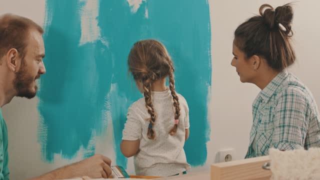 vídeos de stock e filmes b-roll de couple letting their toddler paint the wall with them - sala de casa