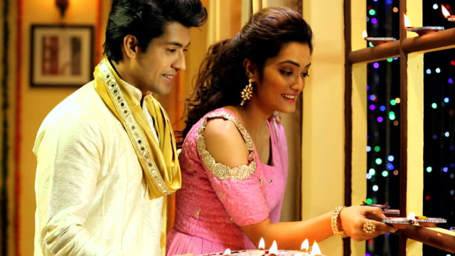 ms pan couple lighting up oil lamp during diwali festival at home - 盆点の映像素材/bロール