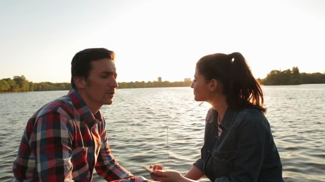 coppia ascoltare la musica in un parco al tramonto. - coppia di adolescenti video stock e b–roll