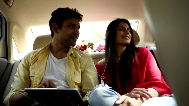 Couple listening music on digital tablet in the car, Delhi, India