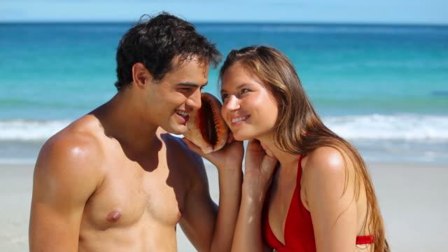 vídeos de stock e filmes b-roll de couple listening to the water with a shell - concha do mar