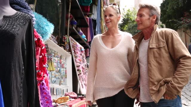 vídeos de stock, filmes e b-roll de couple look at handicrafts on bazaar street - cabelo branco
