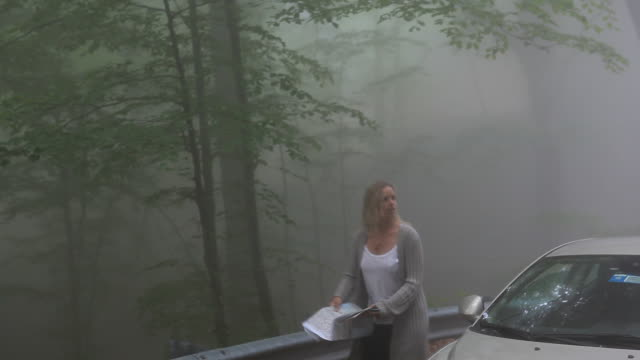 Couple look at road map at edge of foggy road