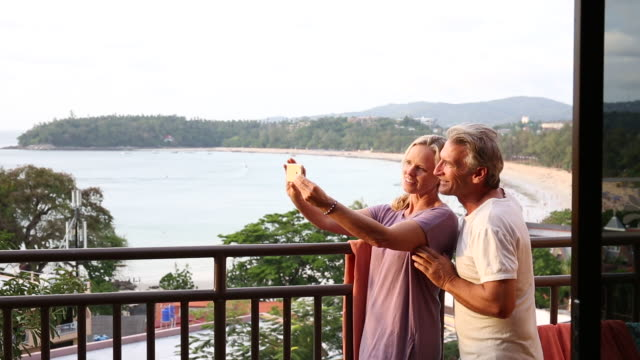 vídeos y material grabado en eventos de stock de couple look off from deck above beach, take smart phone selfie - 55 59 años