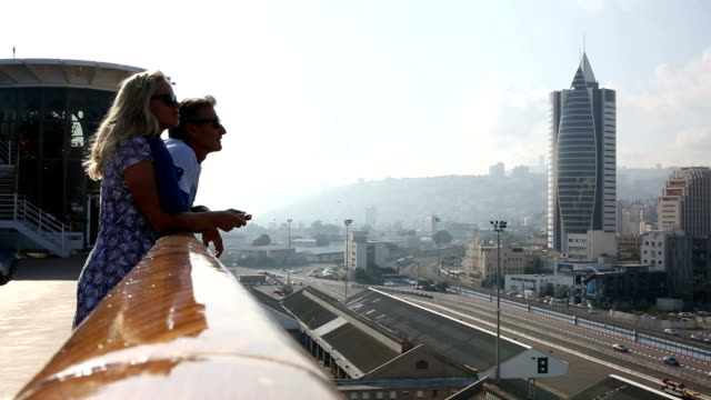 couple look off ship railing to city below, haifa, israel - haifa stock videos and b-roll footage