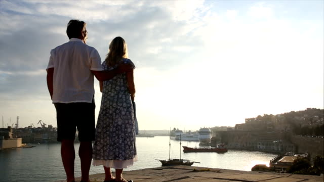 couple look out across harbour, valletta, malta - valletta stock videos & royalty-free footage